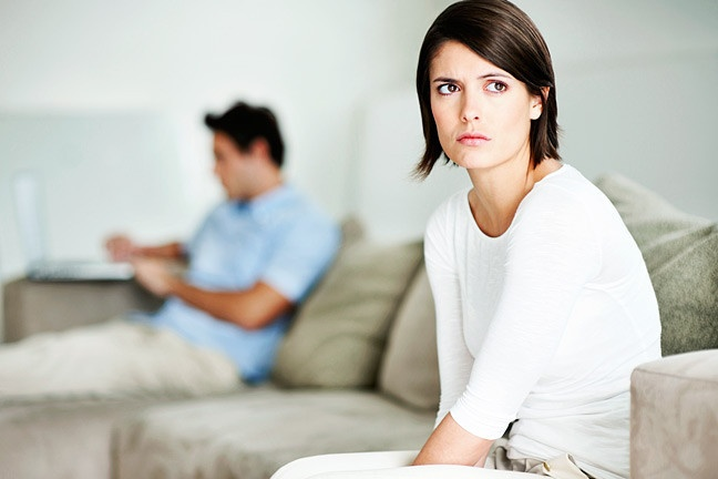 Woman looking away and man working on laptop